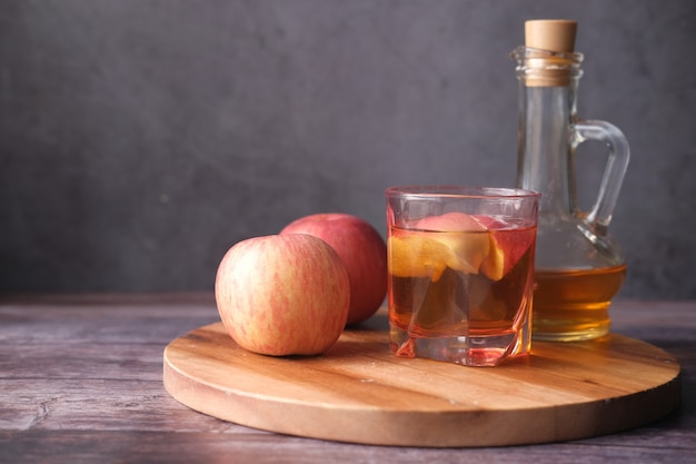 Apfelessig in glasflasche mit frischem grünem apfel auf dem tisch
