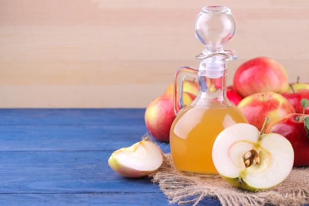 Apfelessig mit äpfeln auf einem hölzernen hintergrund