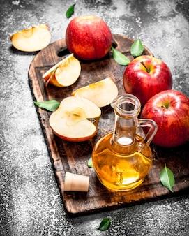 Apfelessig mit frischen äpfeln auf schneidebrett