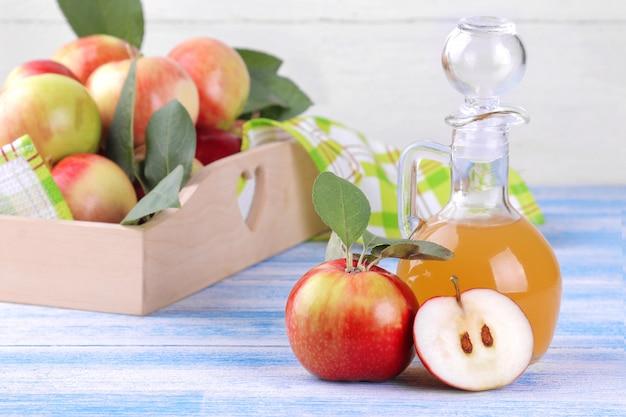 Apfelessig mit frischen reifen äpfeln auf einem hölzernen hintergrund