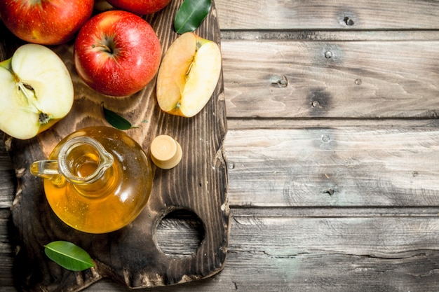 Apfelessig mit frischen roten äpfeln auf einem schneidebrett. auf grauem hölzernem hintergrund.