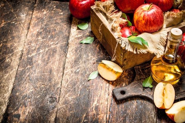 Apfelessig, rote äpfel auf holztisch.