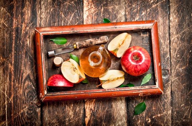 Apfelessig, rote äpfel im alten tablett. auf holztisch.