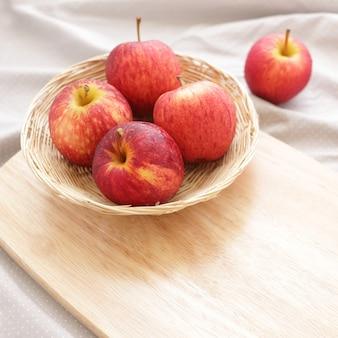 Apfelfrucht im korb mit hölzernem hackklotz
