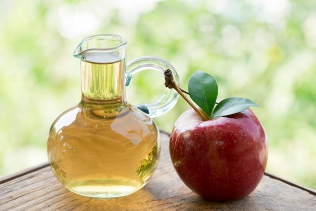 Apfelfrucht und apfelessig auf naturhintergrund.