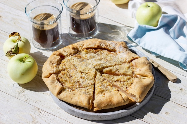 Apfelgalette mit haselnussstreusel, serviert mit kaffee auf holzhintergrund. rustikaler stil.