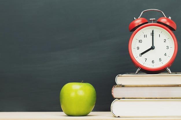 Apfelgrün, wecker rot auf buch, auf den schreibtisch hölzernes briefpapier tafel setzen
