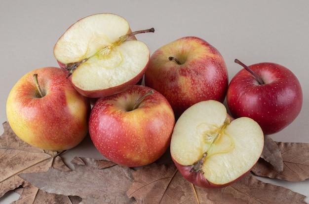 Apfelhaufen und platanenblätter auf marmor