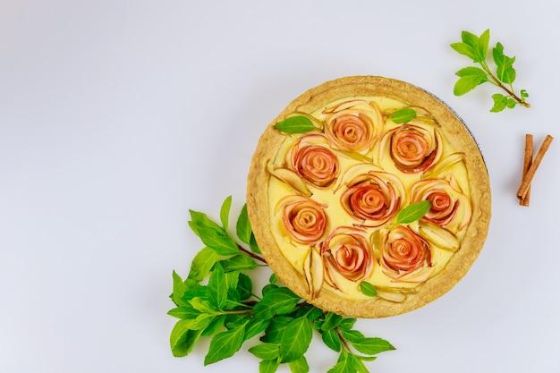 Apfelkäsekuchen mit apfelform in rosenform und frischen äpfeln. draufsicht.