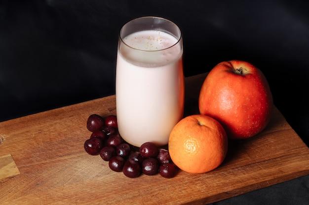 Apfelkirsch-zitrus-smoothie auf einem holzbrett mit früchten auf einer schwarzen oberfläche