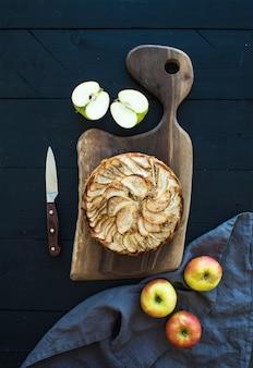 Apfelkuchen auf dunklem hackendem brett