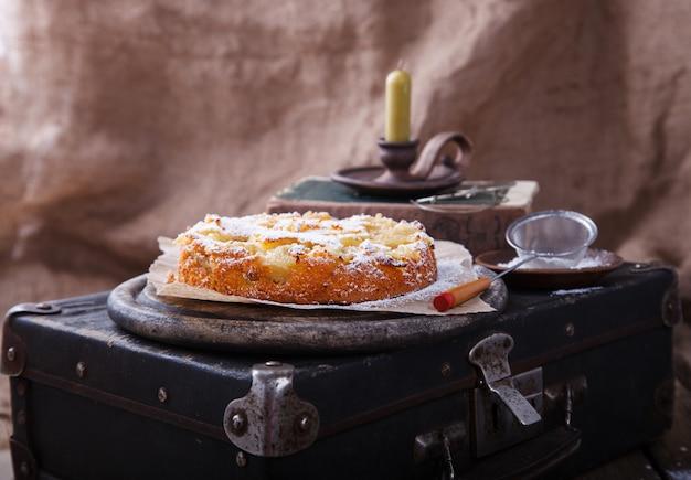 Apfelkuchen auf einem weinlesekoffer in puderzucker