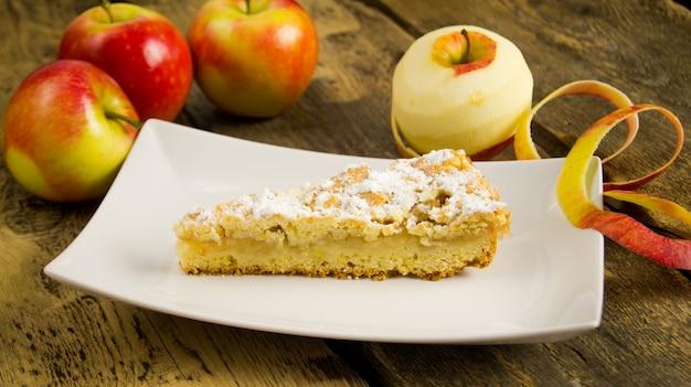 Apfelkuchen auf einem weißen teller auf einem holztisch, äpfel im hintergrund