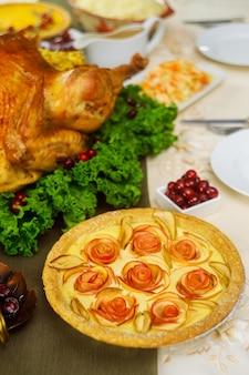 Apfelkuchen auf festlich gedecktem tisch mit truthahn zum erntedankfest.
