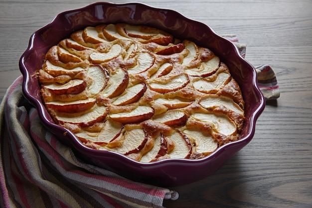 Apfelkuchen in einer keramikschale auf einer holzoberfläche.