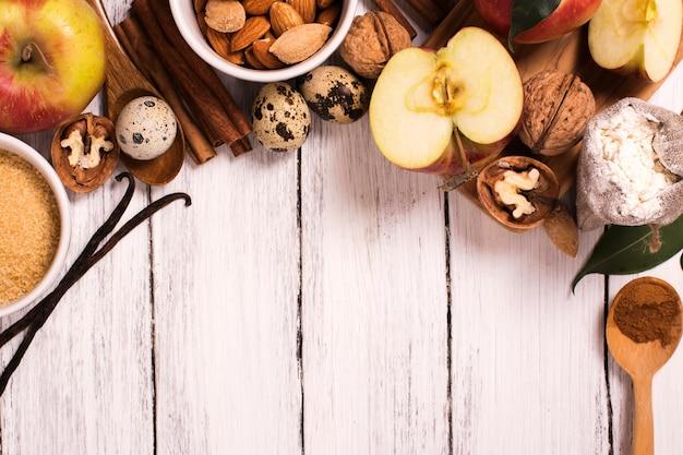 Apfelkuchen ingredients über weißem hölzernem