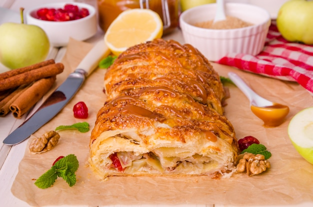 Apfelkuchen mit getrockneten kirschen, walnüssen, zitronenschale und zimt auf weißem hölzernem hintergrund