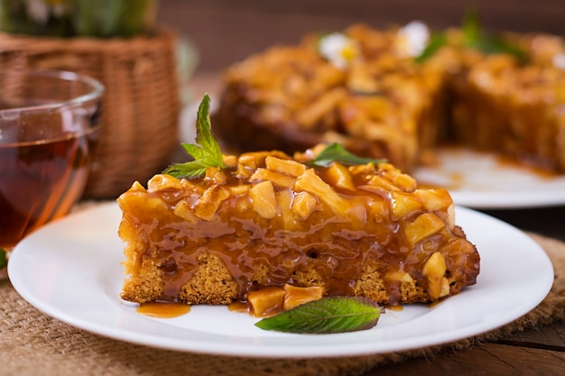 Apfelkuchen mit karamellsoße auf einem hölzernen hintergrund