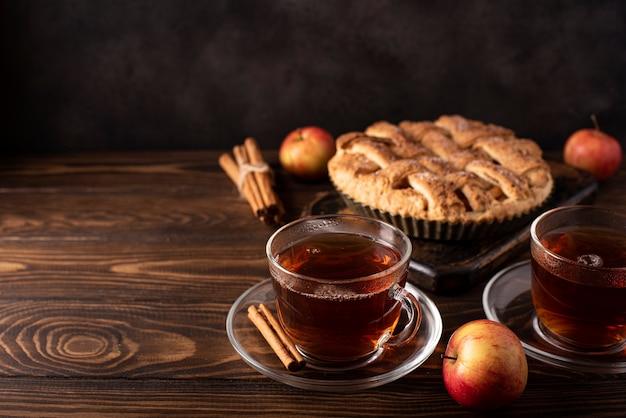 Apfelkuchen mit zimt und heißem schwarzen tee auf einem holztisch