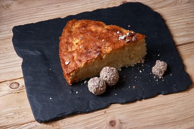 Apfelkuchen-torte auf schieferbrett mit rosinen, nüssen und zimt ist eine vintage hölzerne hintergrundbeschaffenheit. rustikaler stil