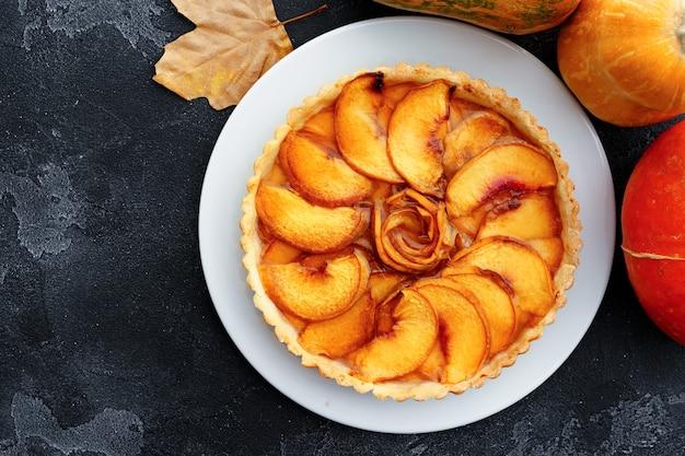 Apfelkuchen torte auf tisch mit kürbis und trockenen blättern dekoriert