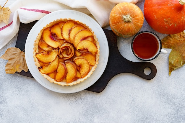 Apfelkuchen torte auf tisch mit kürbis und trockenen blättern