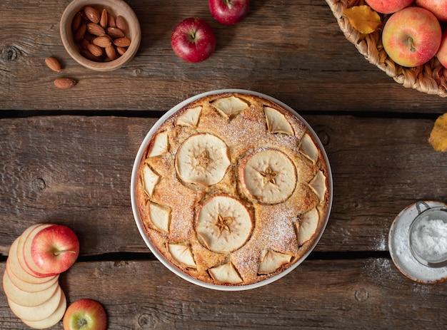 Apfelkuchen um äpfel, blätter, nüsse auf einem hölzernen rustikalen