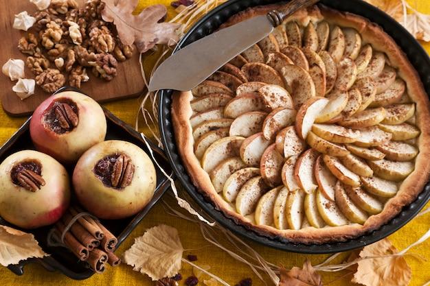 Apfelkuchen und äpfel mit zimt und marmelade gebacken, umgeben von herbstlaub