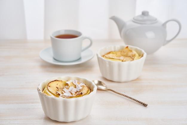Apfelkuchen und tasse tee auf weißem holztisch in der küche