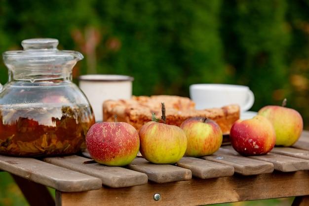 Apfelkuchen und tee auf behälter auf tabelle in einem garten