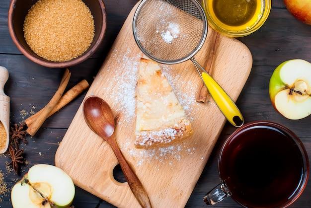 Apfelkuchen und tee auf einem holztisch