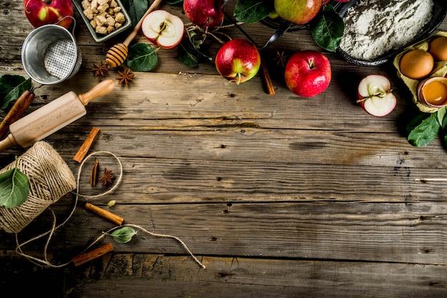 Apfelkuchenbackenhintergrund mit äpfeln, bestandteilen und utencls