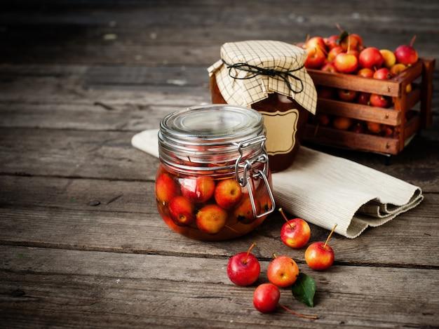 Apfelmarmelade im glas und in den apfelfrüchten. herbstliches stillleben.