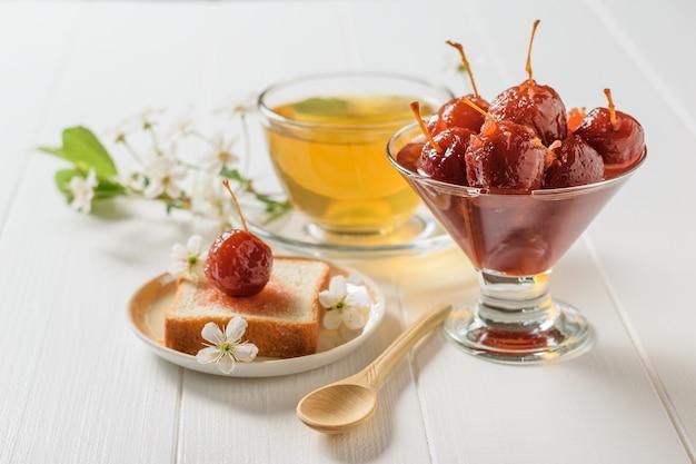 Apfelmarmelade mit tee und brot auf dem weißen tisch.