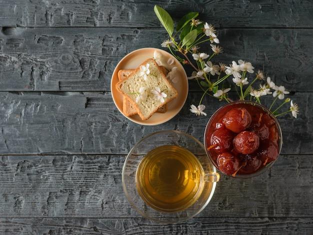 Apfelmarmelade, tee, brot und ein zweig kirschblüten auf einem dunklen tisch.