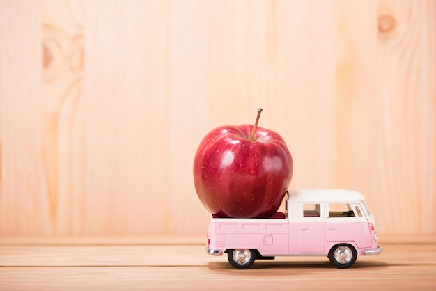 Apfelrot auf spielzeugauto mit holzfußbodenhintergrund
