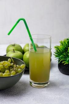 Apfelsaft der frontalansicht in einem glas mit einem grünen strohhalm mit grünen trauben und grünen äpfeln in schalen auf einem weißen hintergrund