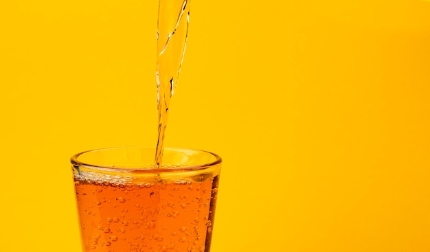 Apfelsaft, der in das glas, getrennt auf gelb gießt
