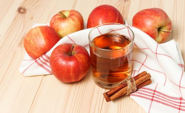 Apfelsaft im glas mit zimtstangen und rohen äpfeln