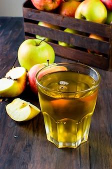 Apfelsaft in einem glas und reifen äpfeln auf einem holztisch