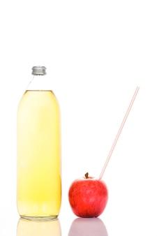 Apfelsaft in einer glasflasche und apfel mit strohhalm