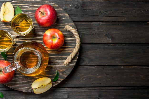 Apfelsaft in einer glaskaraffe auf einem holzdressing mit frischen äpfeln. auf holz.