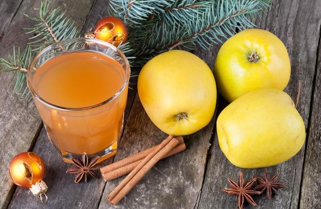 Apfelsaft in glas, äpfeln, gewürzen und tanne auf dem alten hölzernen hintergrund