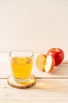 Apfelsaft mit roten apfelfrüchten auf holzhintergrund