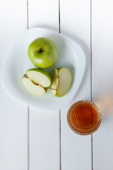 Apfelsaft von den grünen äpfeln auf einem weißen hölzernen backgroundd