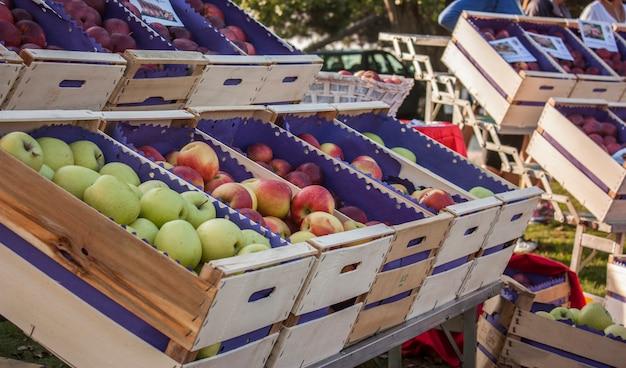 Apfelschachteln in verschiedenen qualitäten und farben auf dem markt zum verkauf bereit.