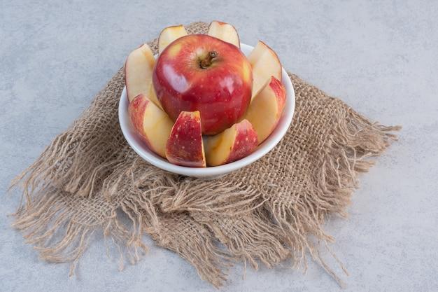 Apfelscheiben und ganzer apfel in weißer schüssel.