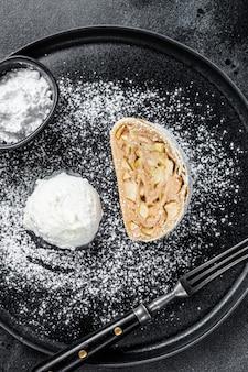 Apfelstrudel mit zimt, puderzucker und vanilleeis auf einem teller. schwarzer hintergrund. draufsicht.
