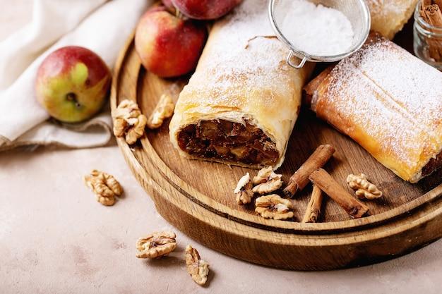 Apfelstrudel serviert mit frischen äpfeln, zimtstangen und walnüssen über weißem texturhintergrund