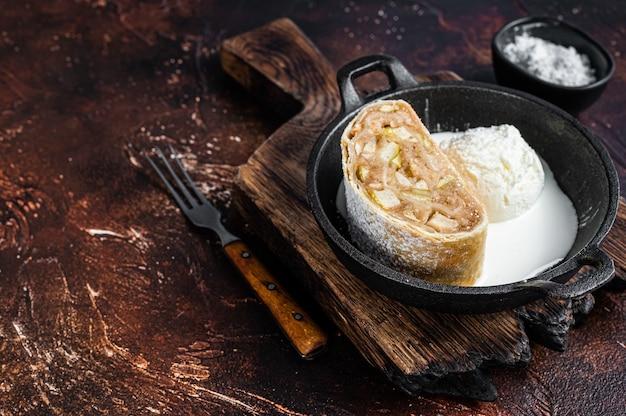 Apfelstrudelstrudel mit zimt, puderzucker und vanilleeis in einer pfanne. dunkler hintergrund. ansicht von oben. platz kopieren.
